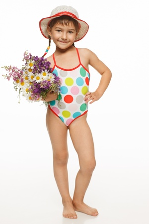 little girl posing: Full length of lovely little girl in in swim wear holding a bunch of field flowers, over white background