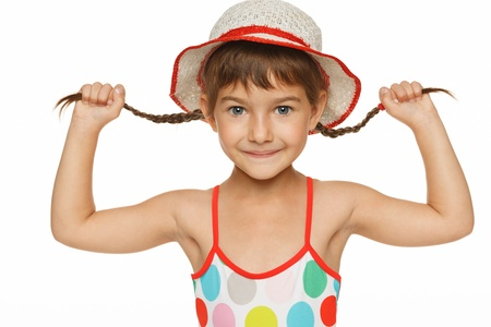 Playful girl in swimming wear holding her braids, over white background photo