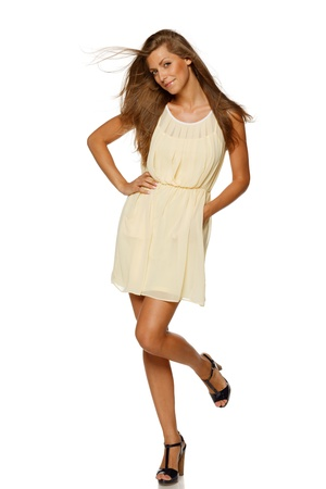 Full length of young elegant female in light yellow summer dress, over white background photo
