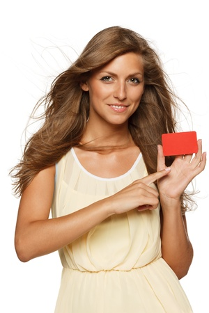 Beautiful woman in yellow dress holding empty credit card and pointing at it,  isolated on white background photo