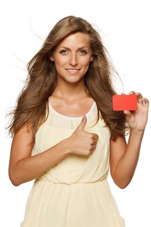 Beautiful woman in yellow dress holding empty credit card and showing thumb up sign,  isolated on white background Stock Photo - 16761870