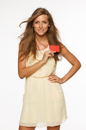 Beautiful woman in light summer dress holding empty credit card isolated on white background photo