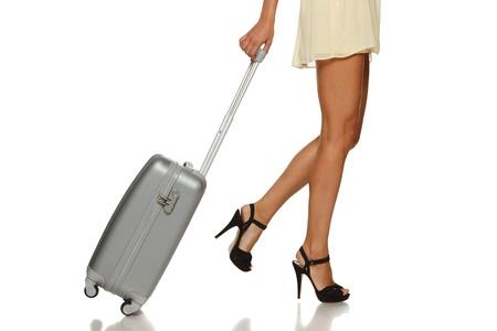 bagage: Vue de c�t� de jambes de femme avec une valise sur le fond blanc