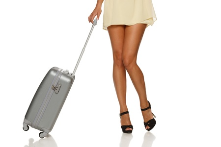 Front view of woman legs with a suitcase on the white background photo