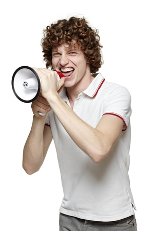 Young man yelling into the megaphone, over white background photo