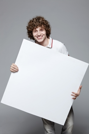Smiling man holding blank banner over gray background Stock Photo - 16796520
