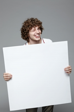 Smiling man holding blank banner over gray background Stock Photo - 16796521
