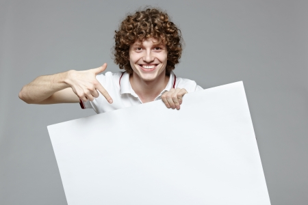 Happy handsome smiling man with banner, over gray background Stock Photo - 16796515