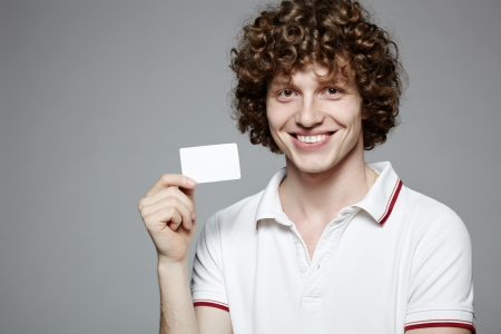 Portrait of the young smiling man holding blank credit card, isolated on gray background photo