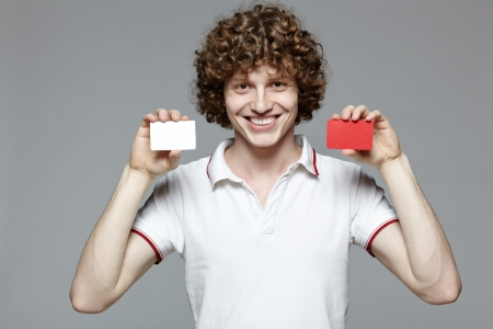 Portrait of the young smiling man holding two blank credit cards, isolated on gray background photo