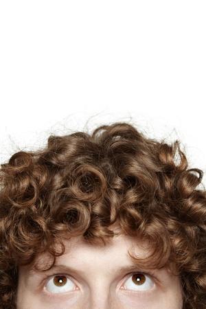 cabello rizado: Imagen recortada de un hombre joven con los ojos mirando hacia arriba, aislado sobre fondo blanco Foto de archivo