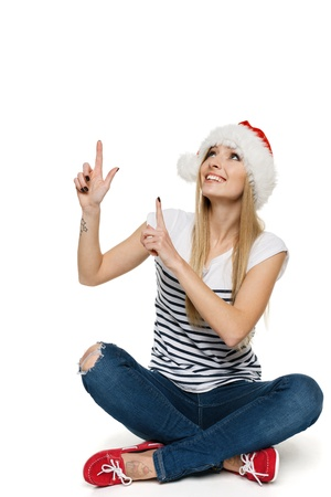 Woman in Santa s hat sitting on floor pointing and looking up, isolated on white background Stock Photo - 17039886