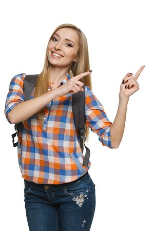 Young smiling female with backpack pointing to the side at blank space for your product or text, over white background  photo
