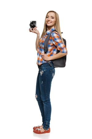 Full length of young female with backpack holding camera over white background photo