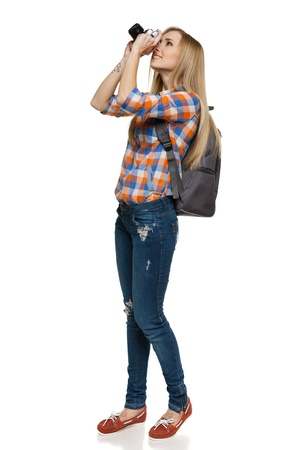 back up: Full length of young female with backpack shooting with camera over white background