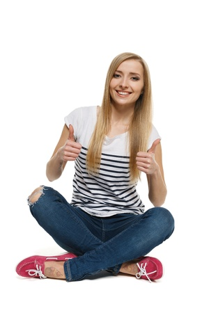 Happy young female sitting on floor showing thumb up signs, isolated on white background photo