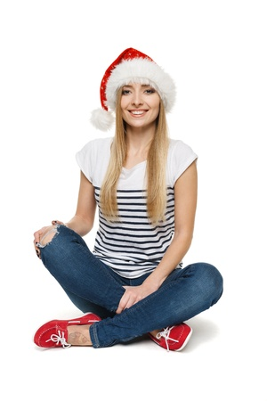Woman in Santa s hat sitting on floor in lotus pose, isolated on white background Stock Photo - 17039892