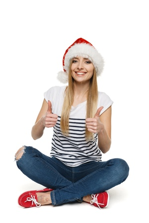 Woman in Santa s hat sitting on floor showing thumb up signs, isolated on white background Stock Photo - 17039855