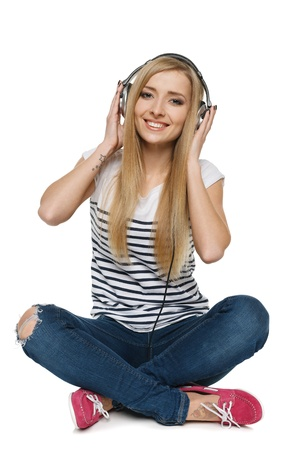 Happy young female sitting on floor enjoying music in headphones, isolated on white background photo