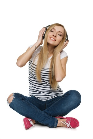 Happy young female sitting on floor enjoying music in headphones with closed eyes, isolated on white background photo