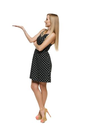 Full length of beautiful woman in dress showing empty copy space on her palm, looking at it, over white background photo