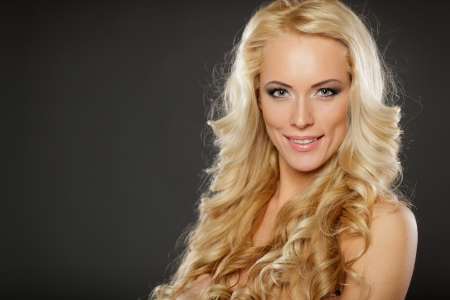 Closeup of beautiful blond female with  beautiful hair, over dark background Stock Photo - 17055107