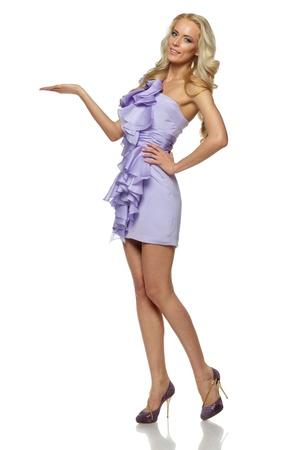 cuerpo entero: Integral de mujer elegante vestido lila en el espacio copia explotación en la palma de su mano abierta, aislada en el fondo blanco Foto de archivo