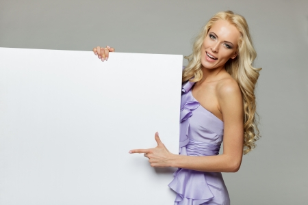Woman pointing at a blank board over gray background photo