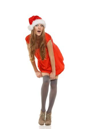 stocking cap: Full length of surprised Santa girl pulling her stockings up, over white background