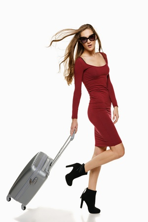Fashionable woman running with suitcase, over white background photo