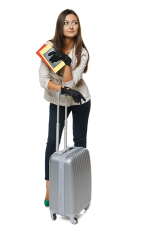 Young female in autumn clothing standing with travel bag, holding passport and tickets,isolated on withe background photo
