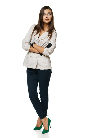 Full length of pensive female in autumn jacket and gloves standing with folded hands and looking to the side, over white Stock Photo