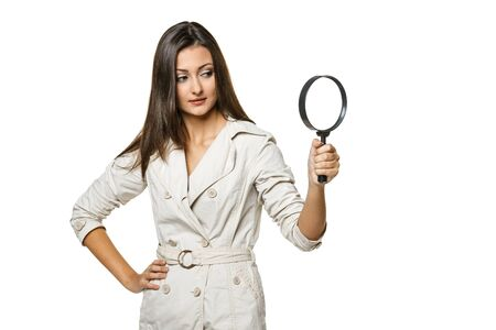 Young female looking through magnifying glass at the blank copy space, over white background Stock Photo - 17098717
