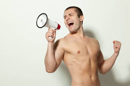 Handsome male model topless yelling into a megaphone Stock Photo - 17157607