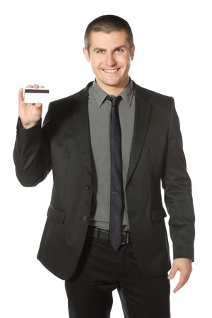 Young smiling businessman holding credit card, isolated on white background photo