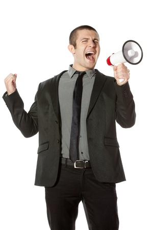 bellowing: Portrait of a young business man yelling into a megaphone  Stock Photo