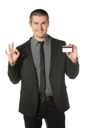Happy businessman with credit card showing OK sign, isolated on white background photo