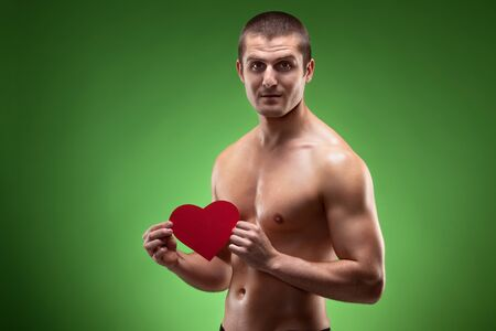 Smiling male model shirtless holding heart shape, over green background Stock Photo - 17281692