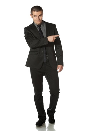 aside: Full length of young business man in suit pointing at copy space over white background Stock Photo