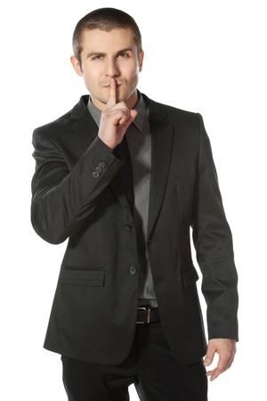 quiet adult: Business man with finger on lips asking for silence over white background Stock Photo