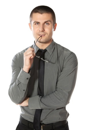 folded hands: Pensive young  businessman holds a pair of glasses, isolated on white background