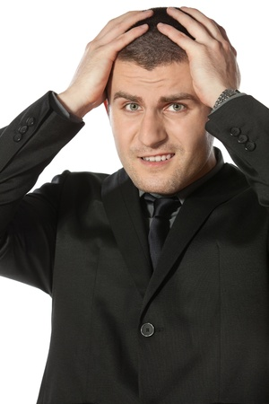 Frustrate young business man holding his head against white background photo