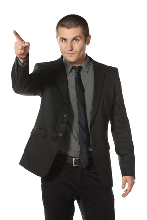 upwards: Young business man in suit pointing at copy space over white background