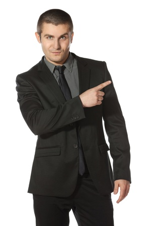 aside: Young business man in suit pointing at copy space over white background