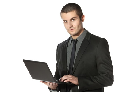 Young businessman working on laptop over white background photo