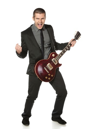 guitarists: Full length of young man in a suit with guitar over white background