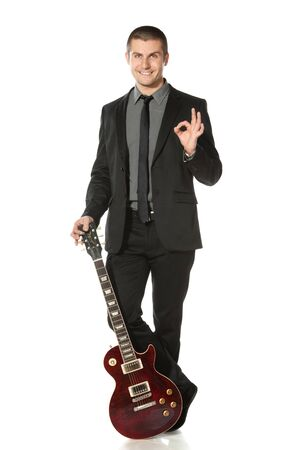 Full length of young man in a suit standing leaning on the guitar showing OK sign over white background photo