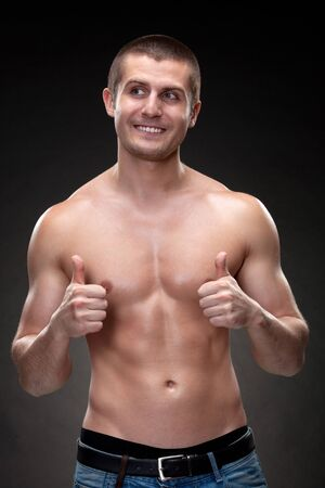 Handsome male with muscular body standing over dark background showing thumb up signs, looking sideways Stock Photo - 17364611