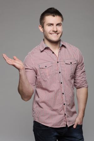 Portrait of handsome young man holding blank copy space on his palm, isolated on gray background Stock Photo - 17411748
