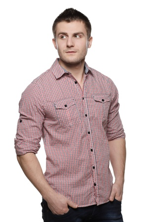 looking sideways: Portrait of pensive young man standing with his hands in pocket looking sideways, isolated on white background